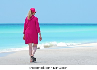 Mature Woman taking a leisure walk on the Beach on a Beautiful Sunny Day.