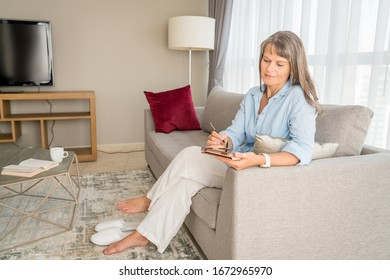 Mature woman taking notes on a tablet in her urban apartment