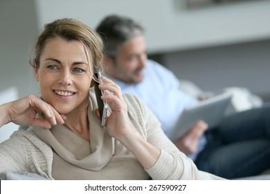 Mature woman talking on smartphone, husband using tablet