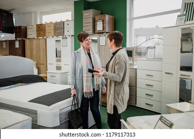 Mature woman is talking to a sales clerk about buying a new mattress.
