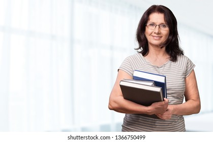 Mature woman teacher with books on background