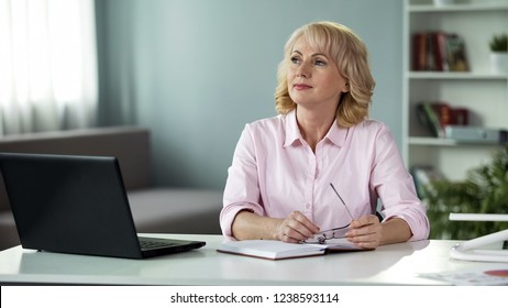 Mature woman thinking with notepad on table, busy housewife, planning of day