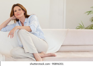 Mature woman in thoughts on the sofa