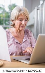 Mature woman touching her laptop and reading a file