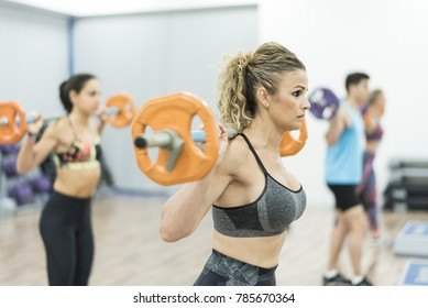 Mature woman training body pump and isometric exercises at gym
