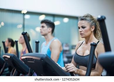 Mature woman training on elliptical bike in gym