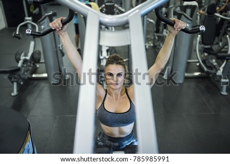 Mature woman training shoulders at gym machines