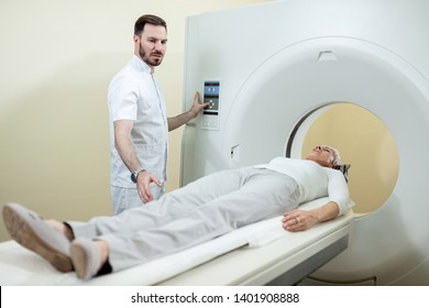Mature woman undergoing for CT scanning while medical technician is supervising the procedure in the hospital.