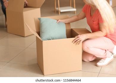Mature woman unpacking moving box at new home