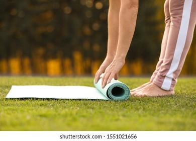 Mature woman unrolling yoga mat outdoors, closeup
