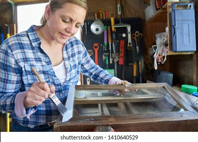Mature Woman Upcycling Furniture In Workshop At Home  Painting Cabinet