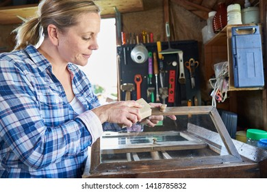 Mature Woman Upcycling Furniture In Workshop At Home Rubbing Down Cabinet With Sandpaper