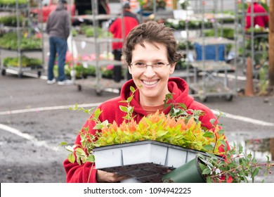 Mature woman at an urban farmers market on an overcast day carrying a tray full of colorful flowers
