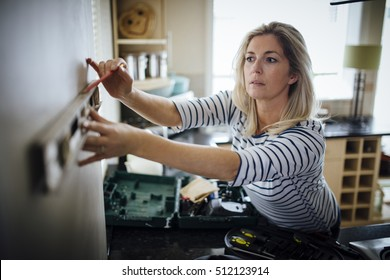 Mature woman using a spirit level and marking the wall with a pencil in her kitchen.