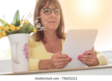 Mature woman using a tablet at home, light effect
