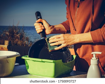 Mature woman washing up dishes in bowl on fresh air. Dishwashing outdoor on camping site, sea shore