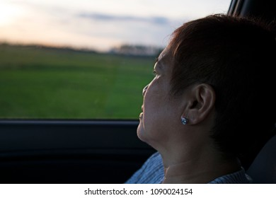 Mature woman watching sunset from inside a car window. Ricefield at the background.
