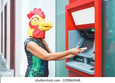 Mature woman wearing chicken mask withdraw money from bank cash machine with debit card - Surreal image of half human and animal - Absurd and crazy concept of ATM advertise