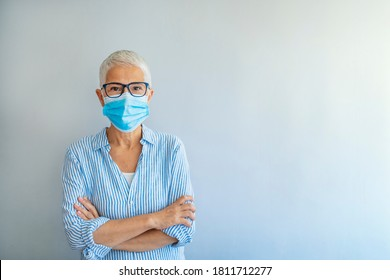 Mature woman wearing a face mask on gray background. Flu epidemic and virus protection concept. Safety during a pandemic, epidemic, seasonal flu. Positive senior woman in medical mask on her face