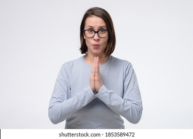 Mature woman wearing glasses keeps palms together, has pleased expression. Glad attractive female makes request, pleads for mercy.