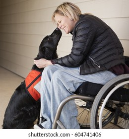 A mature woman wheelchair user with her service dog, a black labrador, leaning in towards each other