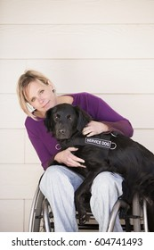 A mature woman wheelchair user with her arms around her service dog, a black labrador whose front paws are on her lap