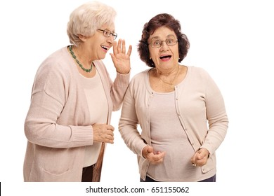 Mature woman whispering to her surprised friend isolated on white background