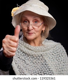 Mature woman in white hat and glasses showing thumb up. Isolated against black background.