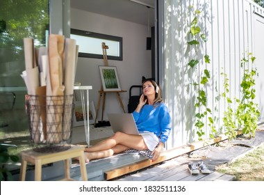Mature woman working in home office in container house in backyard.