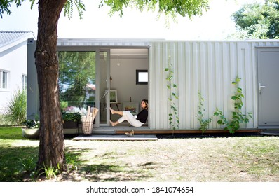 Mature woman working in home office in container house in backyard, resting.