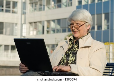 mature woman works with laptop sitting on bech in front of office building
