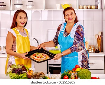 Mature woman with young daughter preparing  pizza at kitchen.
