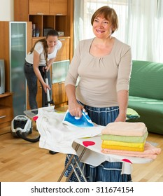 Mature woman and young girl cleaning at home and smiling