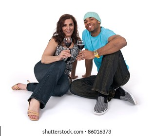 Mature woman with a young man drinking wine, sitting close to each other.
