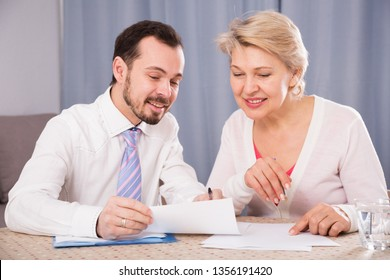 Mature woman and young sales manager signing contract at home