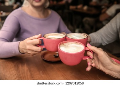 Mature women drinking coffee in cafe, closeup