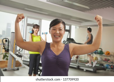 Mature women showing her strength after workout in the gym