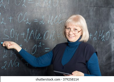 Mature women teacher showing formulas on the blackboard