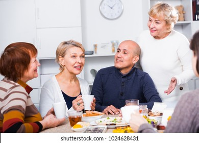 Mature women and their friend are drinking tea and talking at home.