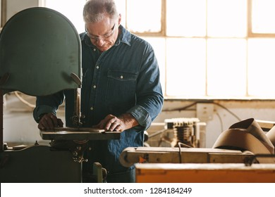 Mature worker in the carpentry workshop cuts the wood using band saw.  Carpenter working in carpentry preparing furniture parts.