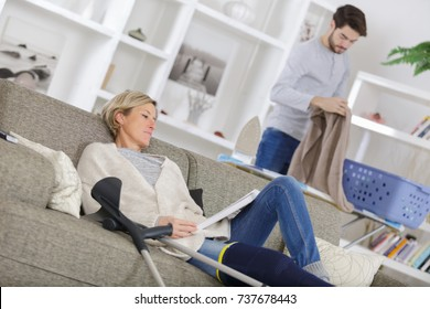 mature wounded woman resting on sofa with carer