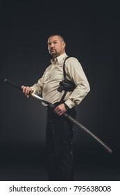 mature yakuza member taking out his katana sword