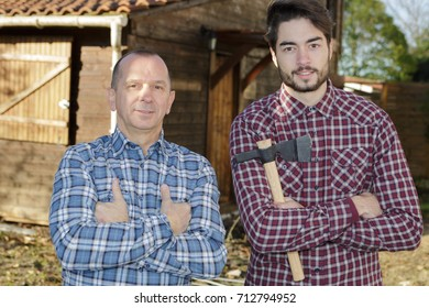 mature and young men posing near wood hut holding axe