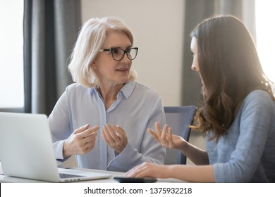 Mature and young women colleagues sitting at desk talking about project startup ideas, sharing thoughts, solve currents issues, make research, discuss growth strategy, think how generate more revenue