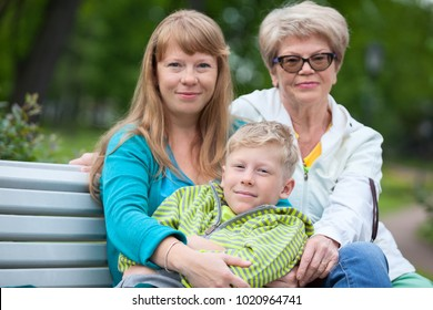 Mature and young women are sitting next to the boy on the bench in urban park