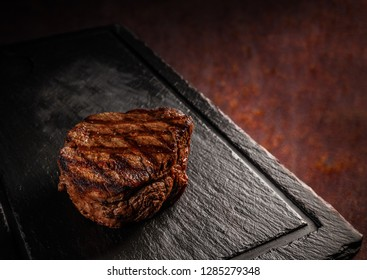 Matured Argentinian ribeye steak on black slate board