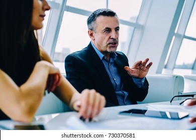 Matured owner of corporation explaining to colleague concepts of business planning gesturing, confident proud CEO talking during conference meeting with investors discussing collaboration details