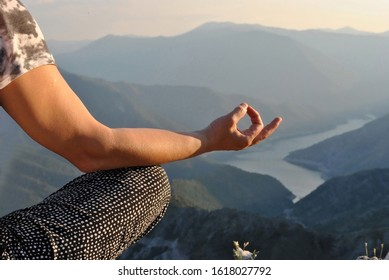 Matured woman in casual clothing practicing yoga outdoor; leg and hand of athlete woman sitting in lotus pose on the top of mountain.
