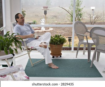 Maturer man in bare feet enjoys his morning coffee in screened porch - spring in Florida.