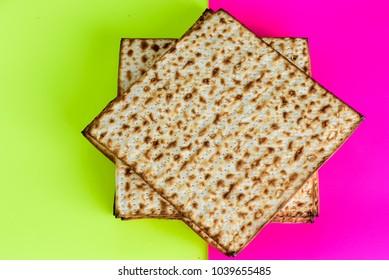 Matza on yellow pink trendy background.Matzah- Jewish traditional Passover unleavened  bread. Pesach celebration symbol.